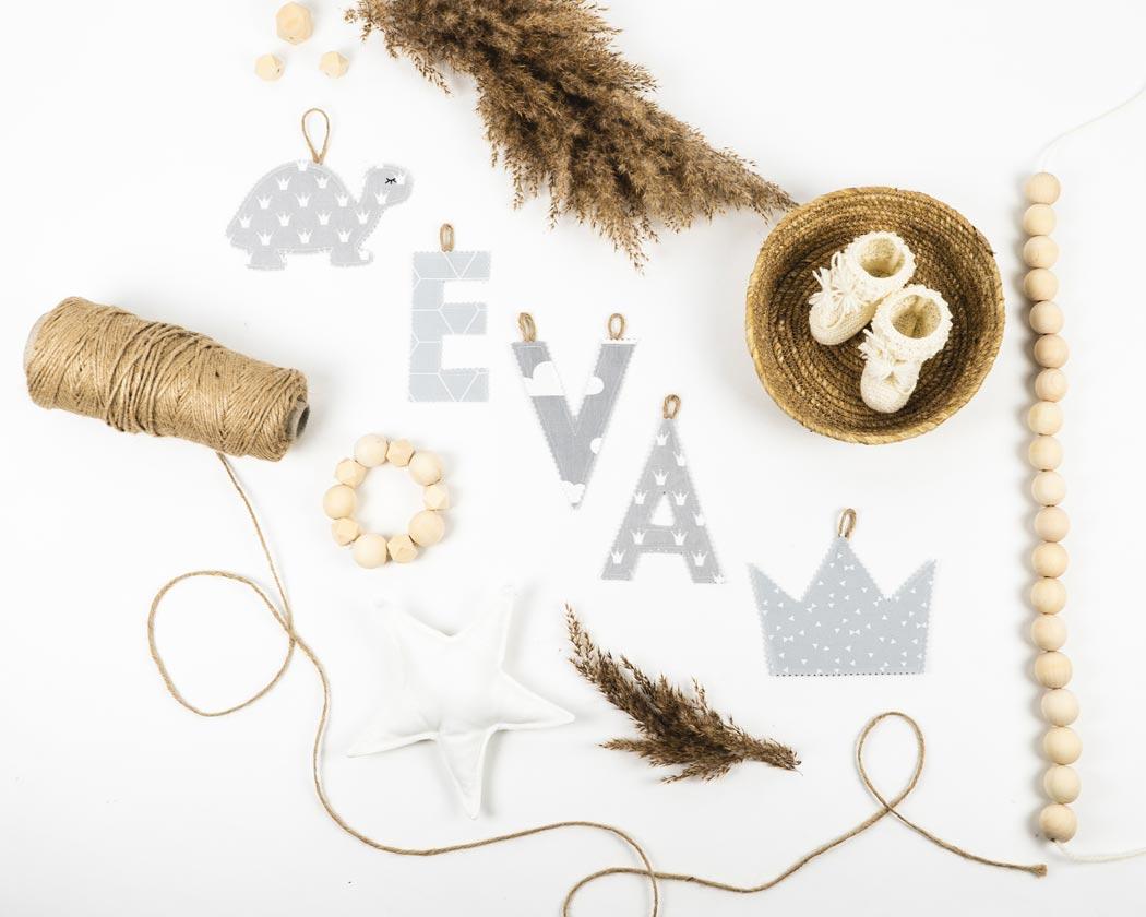 Namensgirlande in hellgrau mit dem Namen Eva. Namensketten sind tolle Geschenke zur Geburt oder Taufe.