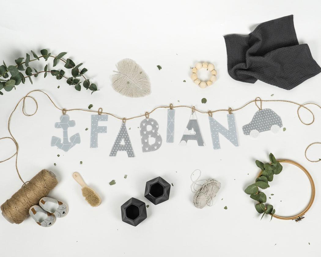 Namensgirlande in hellgrau mit dem Namen Fabian. Namensketten sind tolle Geschenke zur Geburt oder Taufe.
