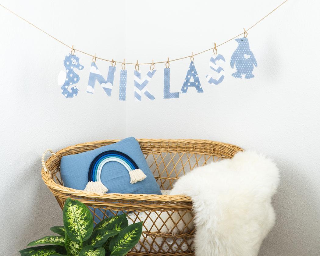 Namensgirlande in pastellblau mit dem Namen Niklas. Namensketten sind tolle Geschenke zur Geburt oder Taufe.