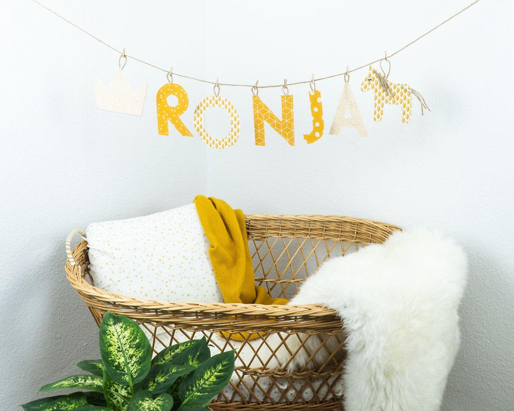 Namensgirlande in ocker mit dem Namen Ronja. Namensketten sind tolle Geschenke zur Geburt oder Taufe.