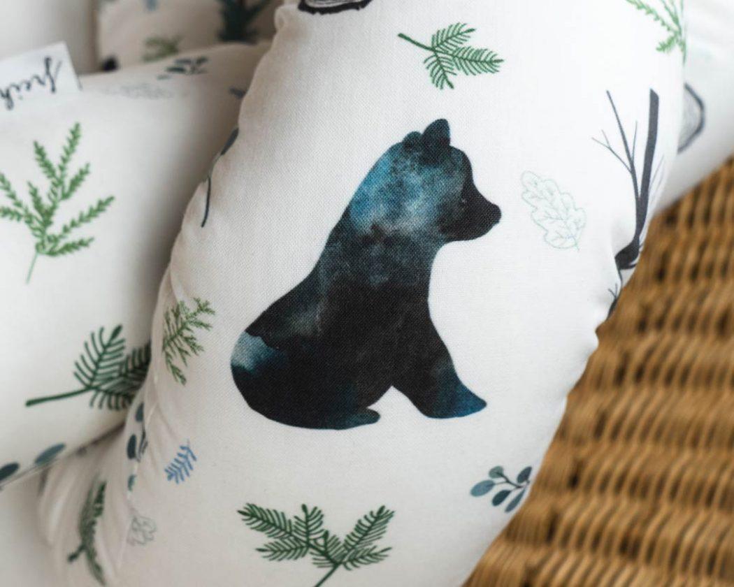 Bettschlange mit Bär als Umrandung im Babybett, schützt sie den Kopf vor Gitterstäben und Zugluft und verhindert, dass der Schnuller aus dem Bett fällt.