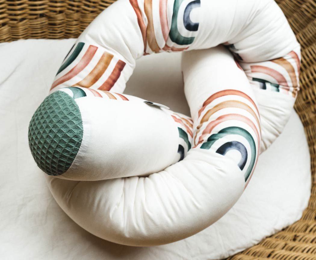 Bettschlange mit Regenbögen als Umrandung im Babybett, schützt sie den Kopf vor Gitterstäben und Zugluft und verhindert, dass der Schnuller aus dem Bett fällt.