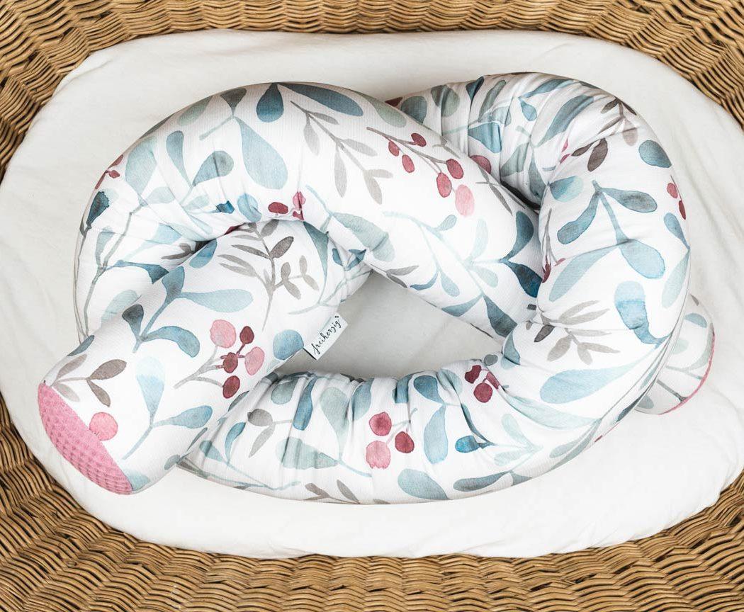 Bettschlange mit roten Beeren als Umrandung im Babybett, schützt sie den Kopf vor Gitterstäben und Zugluft und verhindert, dass der Schnuller aus dem Bett fällt.