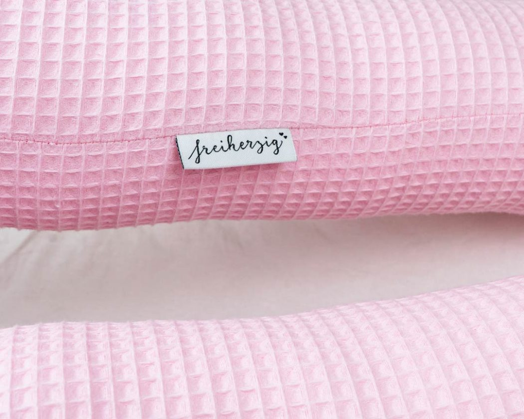 Bettschlange aus Waffelpiqué in rosa als Umrandung im Babybett, schützt sie den Kopf vor Gitterstäben und Zugluft und verhindert, dass der Schnuller aus dem Bett fällt.