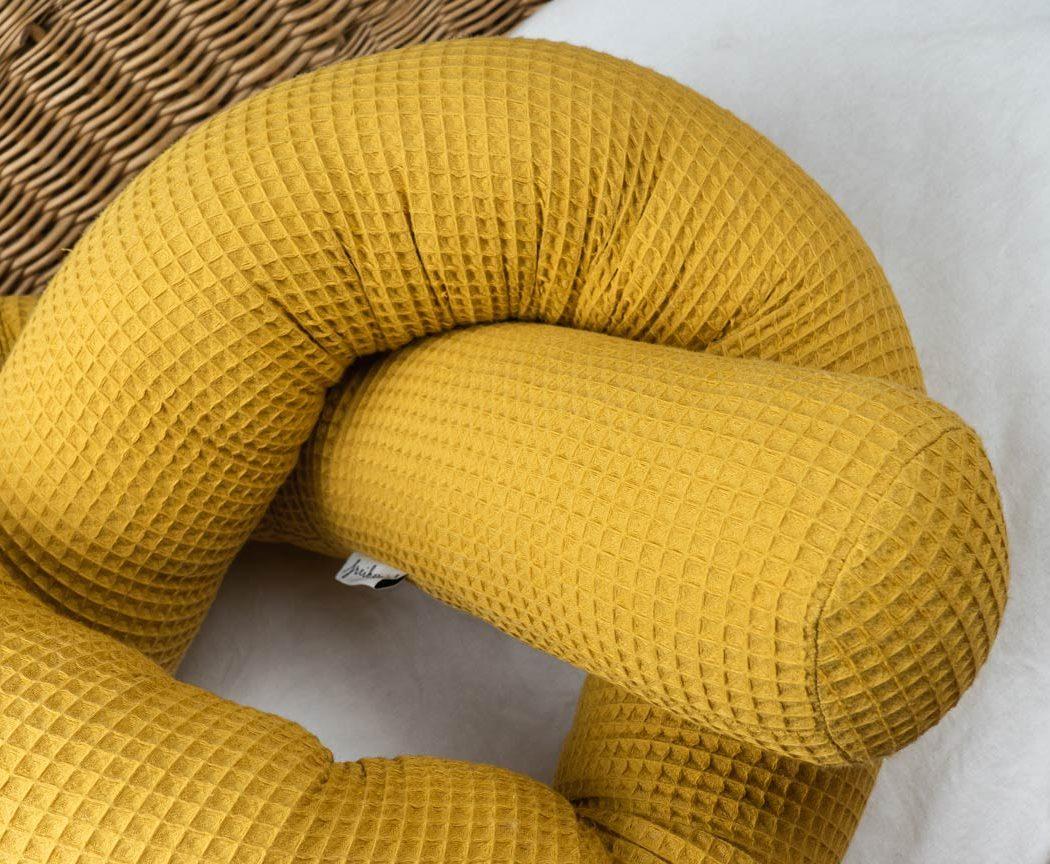 Bettschlange aus Waffelpiqué in senfgelb als Umrandung im Babybett, schützt sie den Kopf vor Gitterstäben und Zugluft und verhindert, dass der Schnuller aus dem Bett fällt.