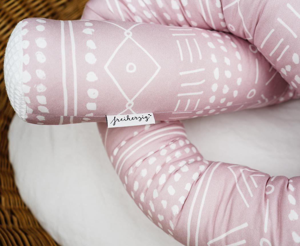 Bettschlange Boho in rosa als Umrandung im Babybett, schützt sie den Kopf vor Gitterstäben und Zugluft und verhindert, dass der Schnuller aus dem Bett fällt.
