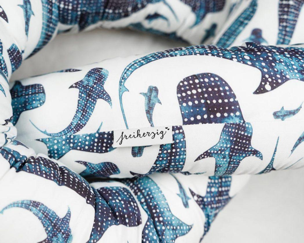 Bettschlange mit Walhaien als Umrandung im Babybett, schützt sie den Kopf vor Gitterstäben und Zugluft und verhindert, dass der Schnuller aus dem Bett fällt.