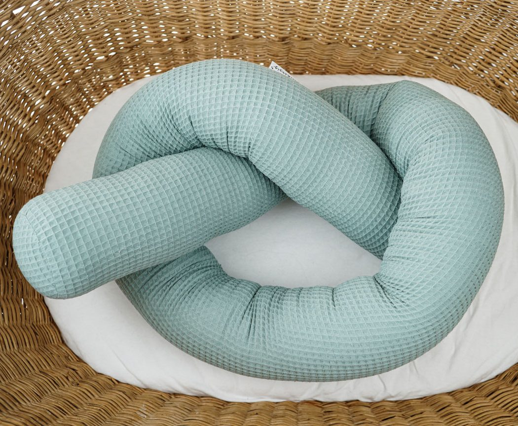 Bettschlange aus Waffelpiqué in grün als Umrandung im Babybett, schützt sie den Kopf vor Gitterstäben und Zugluft und verhindert, dass der Schnuller aus dem Bett fällt.